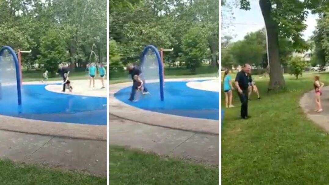 Policjant przebiega z dziećmi przez fontannę w parku